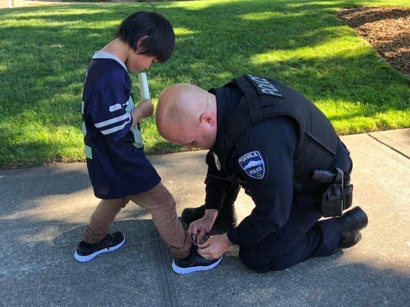 華盛頓塔克維拉警局公布一張照片,一名警察左腳跪地,彎下身來為一名穿著藍色球衫、棕色長褲的黑髮男童綁鞋帶,男童右手則拿著冰棒。(圖取自Tukwila Police Department臉書www.facebook.com/TukwilaPD/)
