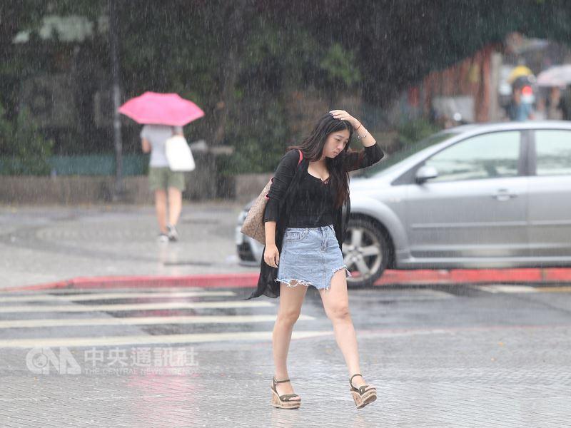 今年第10號颱風安比外圍環流及對流雲系發展旺盛,中央氣象局21日對全台17縣市發布大雨特報。台北市區午後降雨,一名民眾僅以手遮擋頭部在雨中前行。中央社記者徐肇昌攝 107年7月21日