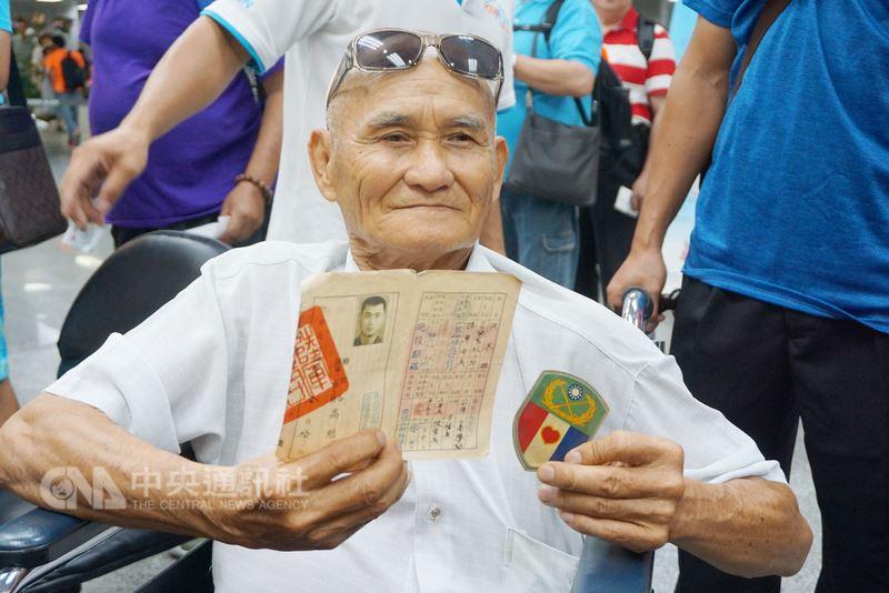 曾於金門服役、現年75歲的洪末雄21日乘坐輪椅,在親友陪同下來到金門,準備重溫早年回憶,他在機場開心展示當年的臂章和退伍令等。中央社記者黃慧敏攝 107年7月21日