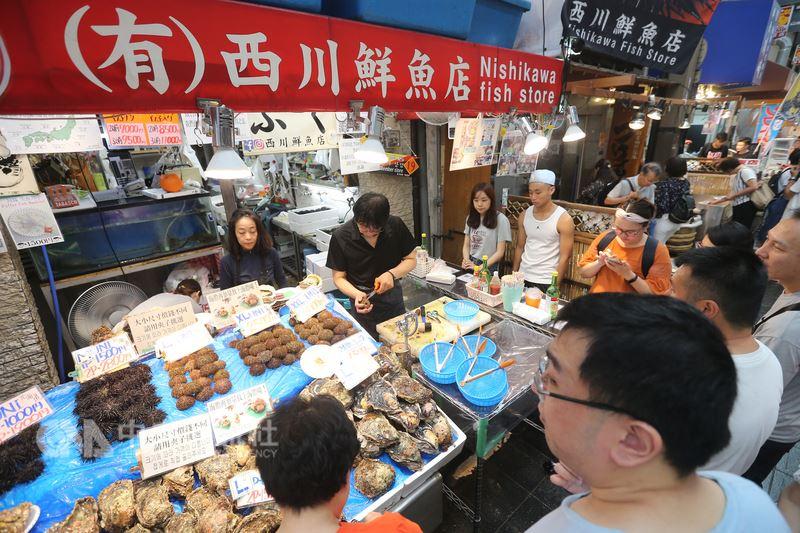 日本「黑門市場」隨著近年觀光客增加,販賣方式也起了變化,許多老店家除了賣生鮮食材,也提供現場料理服務,供遊客能直接品嘗、邊走邊吃。中央社記者徐肇昌攝 107年7月22日
