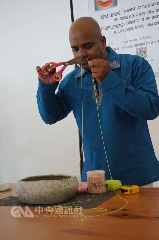 來自印度的瑜珈老師古威傑(Vijay)接受台灣瑜珈業者邀約,22日挑戰2項金氏世界紀錄,將棉繩自鼻進口出以及口進鼻出,記錄通過的繩長,挑戰過程已錄影,將送金氏世界紀錄管理團隊審核。中央社記者趙麗妍攝 107年7月22日
