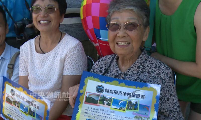 93歲金吳瑞琳阿嬤(右)8日報名參加體驗飛行傘,完成台東鹿野飛行傘區最高齡乘客的挑戰。阿嬤還說,如果可以,100歲還要再搭一次。(業者提供)中央社記者盧太城台東傳真 107年8月8日
