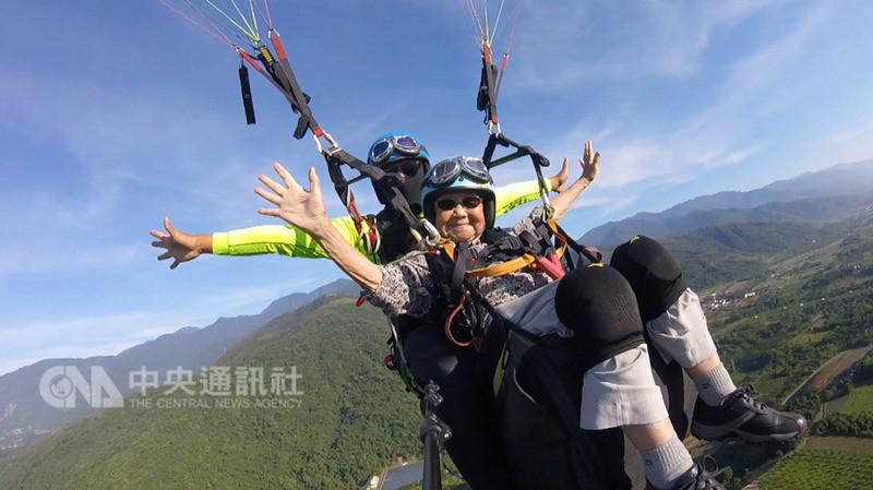 93歲阿嬤金吳瑞琳(前)8日搭飛行傘翱翔千公尺高的台東縱谷上空,毫無畏懼,還像鐵達尼號女主角展開雙臂迎著山風。(業者提供)中央社記者盧太城台東傳真 107年8月8日