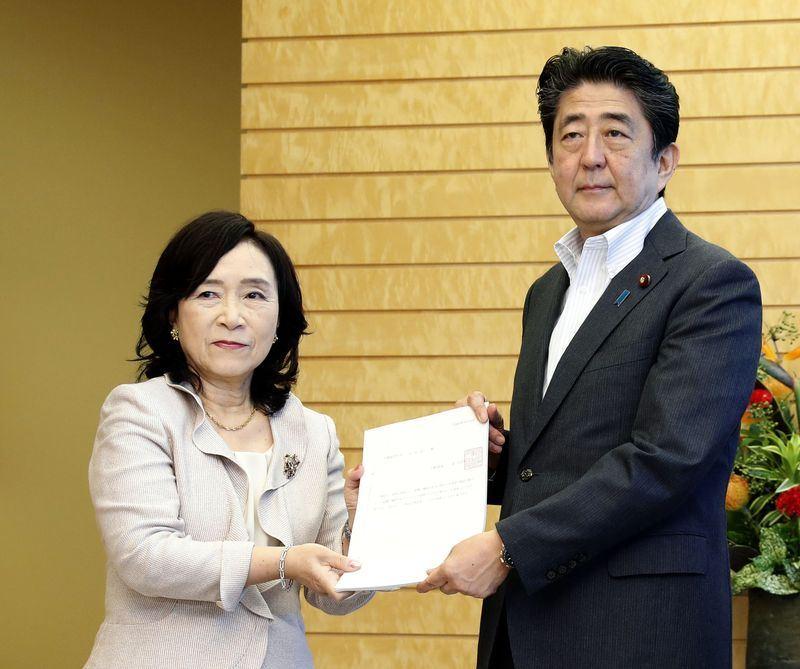 日本人事院10日向國會及內閣提出修法建議,認為國家公務員的退休年齡應延後至65歲。圖為日本首相安倍晉三(右)接過人事院建議書。(共同社提供)