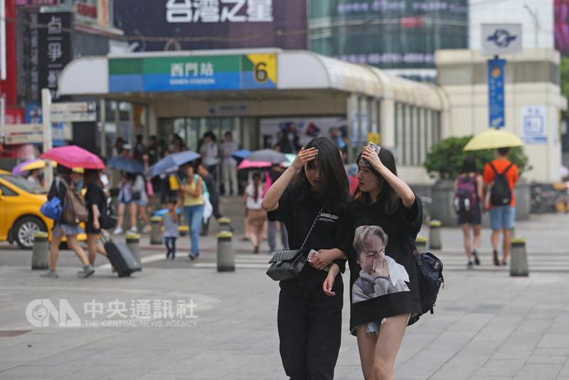 受到西南風影響,中央氣象局14日針對中南部6縣市發布豪雨特報,其他13縣市大雨特報。台北市下午有不定時短暫陣雨,民眾紛紛撐傘遮雨。中央社記者吳家昇攝 107年8月14日