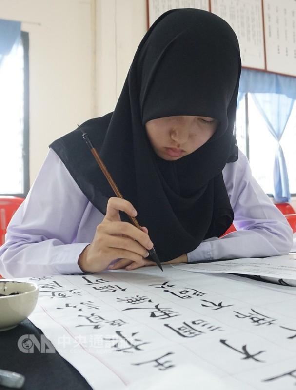 已經舉辦10年的泰北地區正體漢字文化節,以比賽方式鼓勵學生學習。圖為一名清萊穆斯林學生參加書法比賽。中央社記者劉得倉清萊攝 107年8月16日