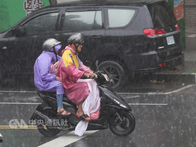 西南風及對流旺盛,中央氣象局19日針對19縣市發布大雨特報,新北市午後瞬間大雨,機車騎士在雨中前進。中央社記者徐肇昌攝 107年8月19日