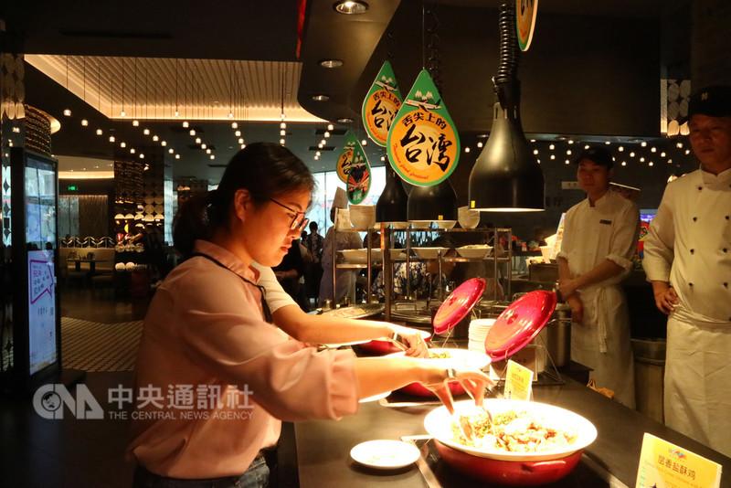 漢來海港餐廳近來舉辦台灣美食節活動,推出40道左右的台灣美食料理,讓來店陸客能「全台吃透透」。業者發現,最受陸客歡迎的菜色是三杯雞、紅糟肉、擔仔麵、蚵仔煎。圖為消費者正在夾取台灣鹽酥雞。中央社記者陳家倫上海攝 107年8月20日