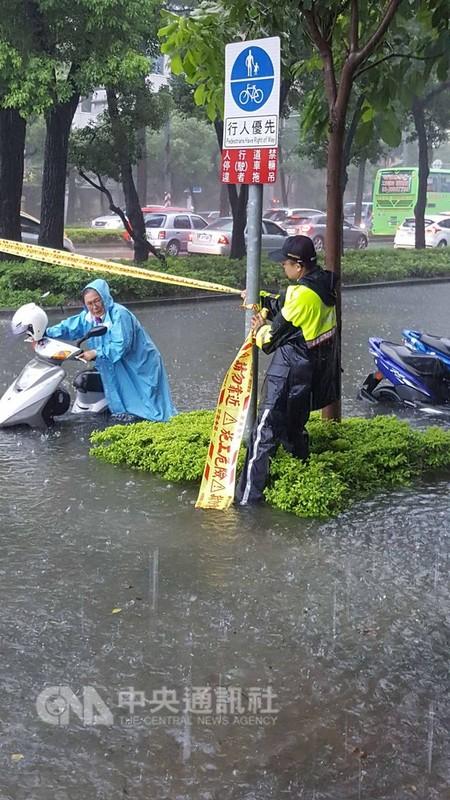 高雄市23日瞬間強降雨不斷,造成多處積水成災,路上有多部汽機車拋錨,交通打結。圖為新興區民生路淹水情形。(警方提供)中央社記者程啟峰高雄傳真  107年8月23日