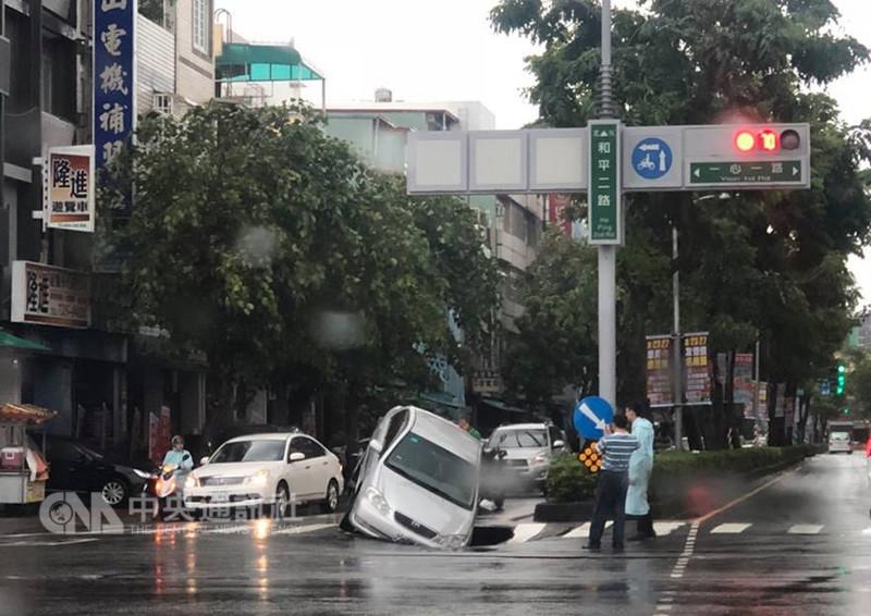 高雄市一心路與和平路口29日發生路面塌陷,波及一輛路過的自小客車,車頭深陷,所幸駕駛並無受傷。(民眾提供)中央社記者程啟峰高雄傳真  107年8月29日