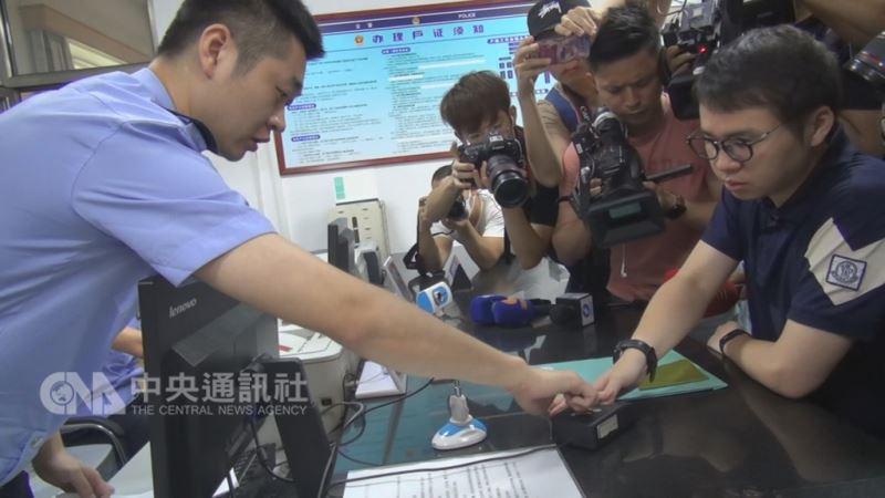 台灣籍的中國首鋼集團「創業公社」總經理鄭博宇(右),1日一早就前往北京市石景山區新古城派出所申辦「港澳台居民居住證」。除繳交證件外,他並在員警導引及媒體見證下留下指紋,完成申辦手續。中央社記者邱國強北京攝 107年9月1日
