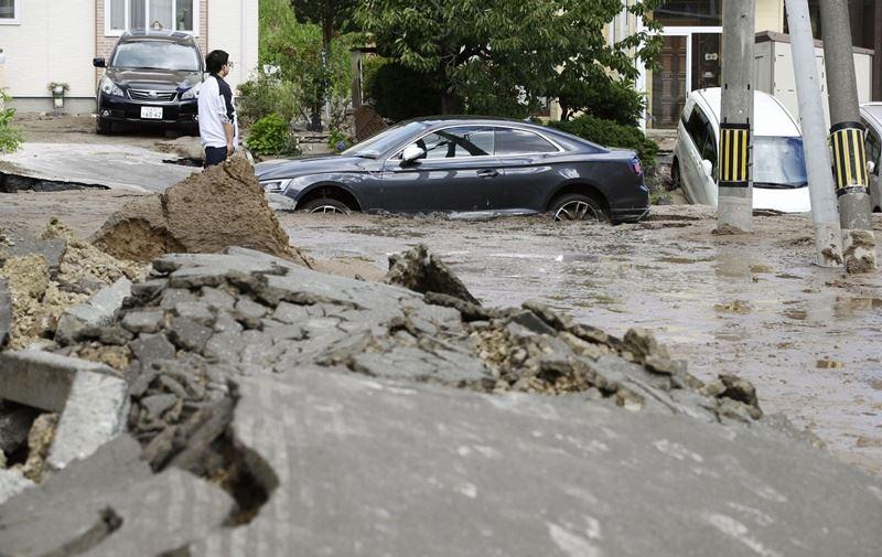 日本北海道6日發生強震,札幌市清田區疑因山坡道路上方陷落造成水管破裂,水和土砂往下流,造成道路下方的汽車陷入泥濘。(共同社提供)