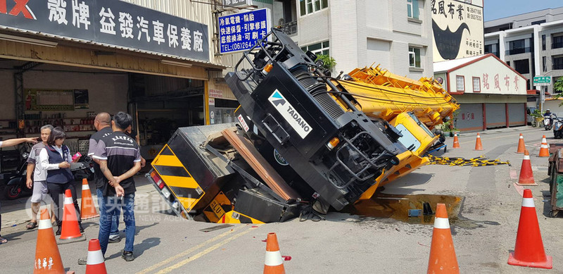 一輛大吊車7日上午在台南市南區利南街準備施工時,疑因地基掏空,突然陷進路面。(台南市政府提供)中央社記者張榮祥台南傳真  107年9月7日