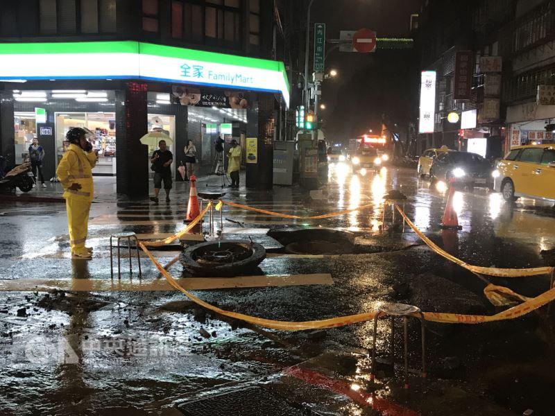 台北市區8日午後下起暴雨,西門町一帶發生從地下噴出水柱沖破人孔蓋意外,造成路面破損,警方獲報到場拉起封鎖線,避免人車誤闖受傷。中央社記者吳翊寧攝 107年9月8日