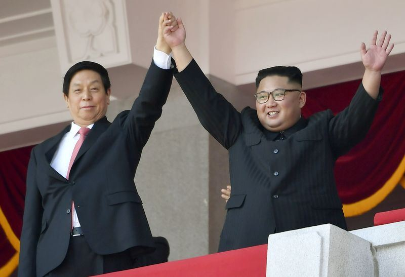 北韓9日在平壤舉行70週年國慶閱兵式,北韓領導人金正恩(右)在觀禮台上,高舉中國全國人大常委會委員長栗戰書(左)的手,向台下的人群致意。(共同社提供)