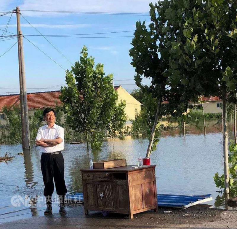 8月下旬,上游3座水庫在暴雨中同時洩洪,山東壽光市因而慘遭淹沒重創,事後未見官員被究責,壽光市委書記朱蘭璽9日卻遭調職。圖為災民拍攝朱蘭璽著雨靴凝望災區的照片,事後受到瘋傳。(取自網路)中央社 107年9月10日