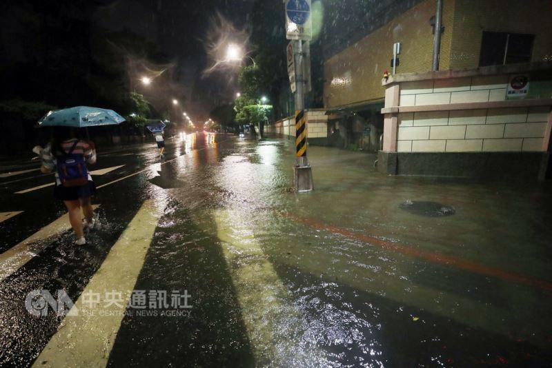 圖為8日台北市中正區貴陽街與公園路交叉口積水深達腳踝,路旁人孔蓋也不停冒水。(中央社檔案照片)