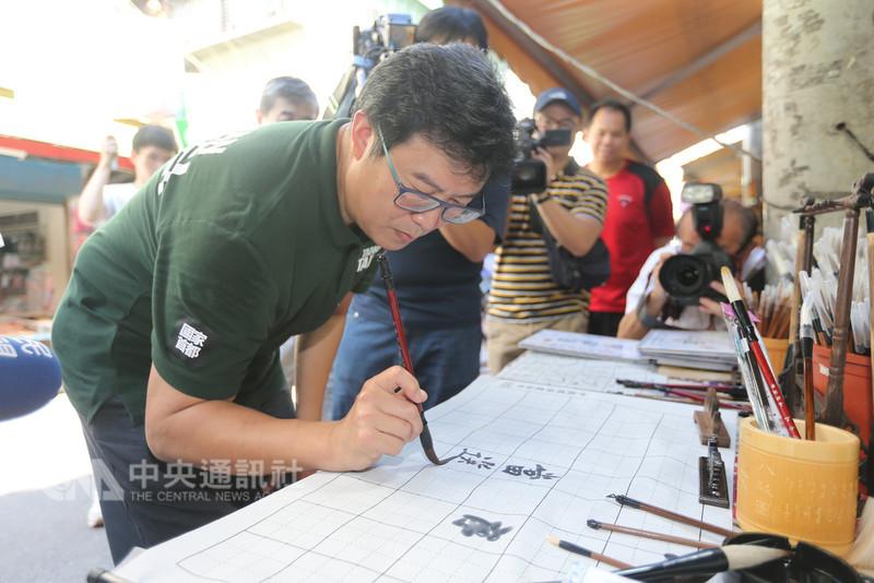 民進黨籍台北市長參選人姚文智(前)13日在北投金龍市場掃街拜票,一時興起,在賣水寫布的攤位,揮毫寫下「當選」。中央社記者徐肇昌攝  107年9月13日