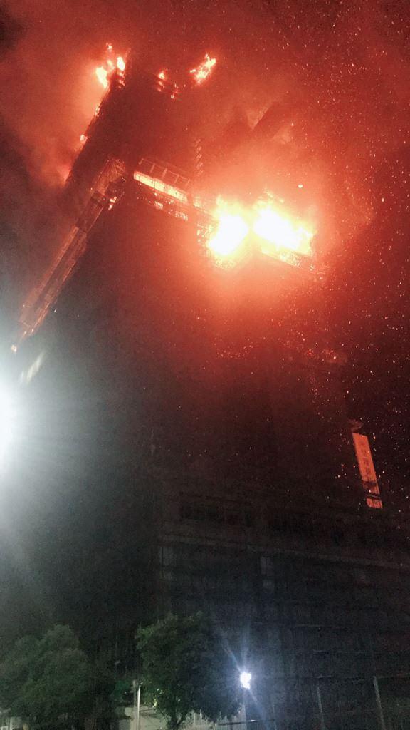 新北市新莊區中央路一處24層樓高、仍在興建中的建築大樓工地13日晚間7時許驚傳火警,火勢猛烈,警消獲報出動大批人車前往灌救,已控制火勢。(警消提供)中央社記者王鴻國傳真 107年9月13日