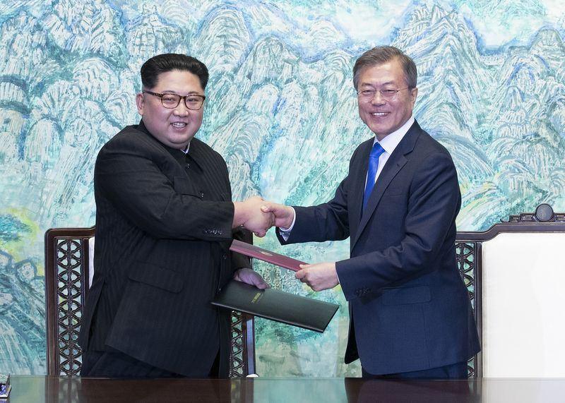南韓總統文在寅(右)將繞道黃海直飛平壤,參加18至20日在平壤舉行的南北韓高峰會談。圖為4月27日文在寅與北韓領導人金正恩簽署後交換板門店宣言。(兩韓峰會共同採訪團提供)