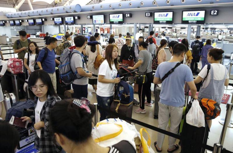 關西機場第一航廈14日起部分重啟,旅客排隊辦理登機手續。(共同社提供)