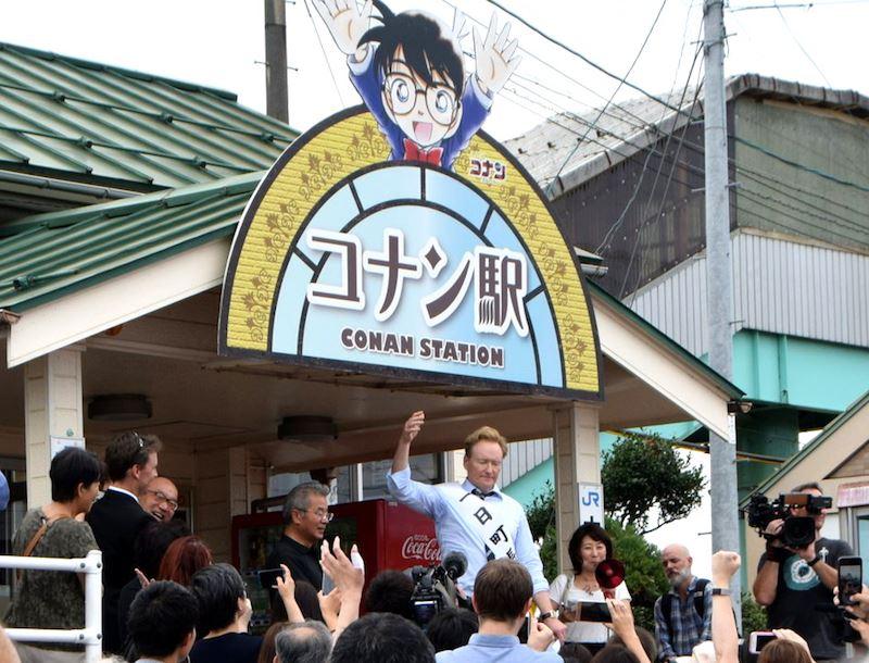歐布萊恩(後排舉手者)6日造訪日本鳥取縣北榮町,在「柯南車站」JR由良站前向歡迎他來訪的民眾致謝。(圖取自北榮町臉書facebook.com/hokuei.town)