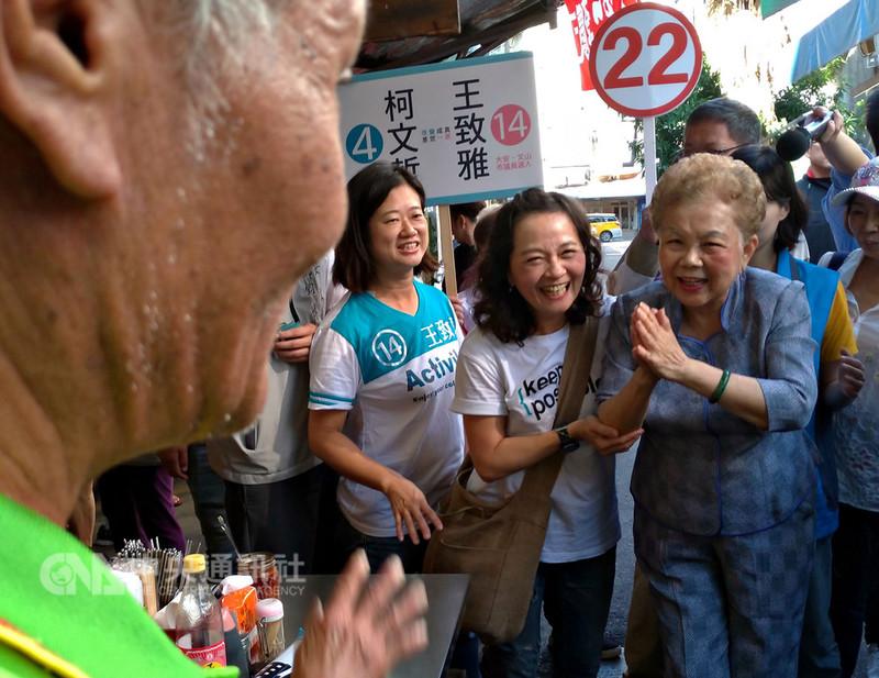 台北市長柯文哲的母親何瑞英(前右)21日前往大安區龍泉市場掃街拜票,向攤商及民眾合十請託。中央社記者陳妍君攝  107年11月21日