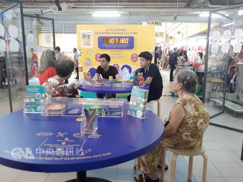 新加坡今年3月擬申請將小販文化列入「非物質文化遺產」,熱情的志工正向旅客或前往用餐的消費者說明申遺的積極意涵。中央社記者黃自強新加坡攝  108年1月23日