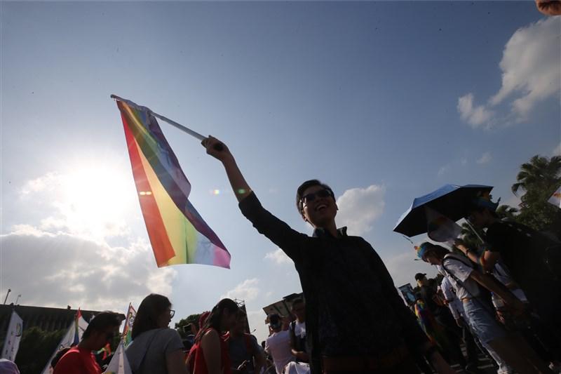 行政院同性婚姻專法草案出爐,大致內容包括讓同志配偶可有合法財產繼承權、醫療權、收養血緣子女、同時也必須遵守單一配偶相關權利義務。圖為參與同志遊行民眾舉起彩虹旗。(中央社檔案照片)