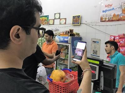 一名男子用Paytm行動軟體掃描條碼在小商店付款。