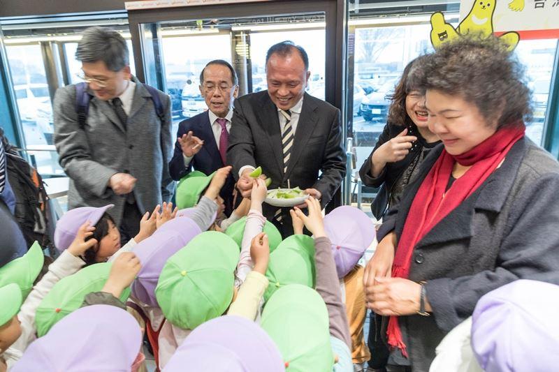 農委會主委林聰賢(中)日前出訪日本,在中日本高速道路株式會社協助下,獲安排在高速公路休息站海老名服務區提供台灣蜜棗試吃,林聰賢說,日本小朋友原本因為沒看過、沒吃過而不太敢試吃,在吃了一口後頻說好吃,並爭著試吃。(農委會提供)中央社記者楊淑閔傳真 107年3月8日