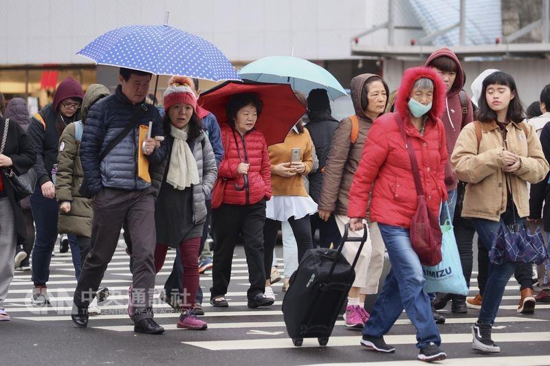 鋒面通過,強烈大陸冷氣團報到,台北市8日下午飄著細雨,氣溫偏低,民眾撐傘並穿著保暖衣物禦寒。中央社記者吳翊寧攝  107年3月8日