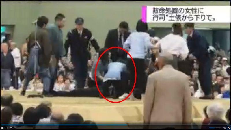 日本舞鶴市長4日在相撲表演場地「土俵」內昏倒,具護士資格的女性(紅圈者)進場急救,卻被裁判以廣播請下來。(圖取自NHK網站www.nhk.or.jp)