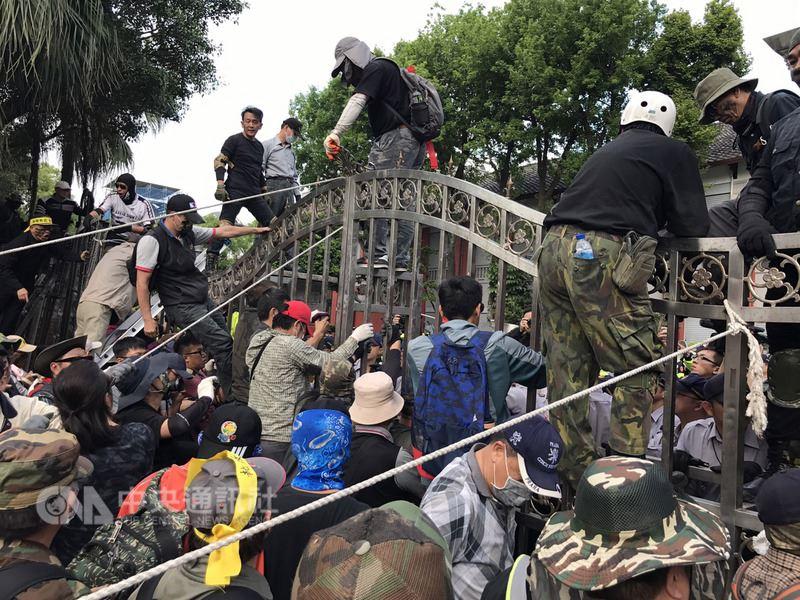 退伍軍人團體25日在立法院周圍抗議軍人年金改革,下午抗議群眾拆除警方布署的拒馬、鐵柵欄,企圖爬進立院大門。中央社記者張新偉攝 107年4月25日
