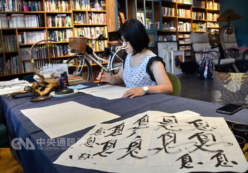 每名造訪瑞芳新村芳書院的旅人,在息書院停歇腳步後,可以在一大張宣紙上揮毫書寫,最後,還需在小紙卡寫上「息」字,透過書法反思探索自己的內心世界。中央社記者黃旭昇新北市攝 107年5月26日