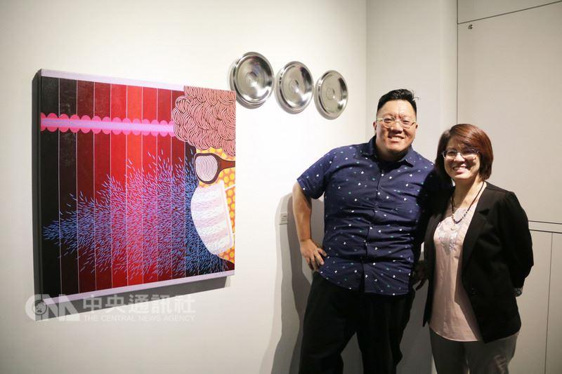 藝術家廖堉安(左)以網路世界作為創作來源,用壓克力顏料、畫布創作與網路議題相關的畫作,透過可愛型、較親近人的動物,例如貓、狗、鴨子、鳥當作擬人的元素,描繪出都會人群的網路世界。(弘光科大提供)中央社記者蘇木春傳真 107年6月12日