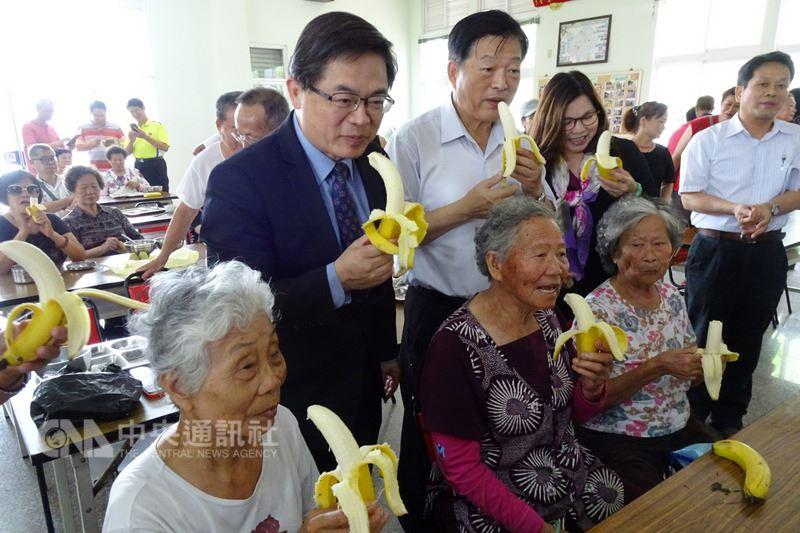 台南市代理市長李孟諺(二排左)13日前往安定區新吉關懷據點,將市府採購的1000公斤香蕉分贈給社福單位,他說,希望有供餐的私人企業也能以香蕉當作餐後水果,幫助農民度過難關。中央社記者楊思瑞攝 107年6月13日
