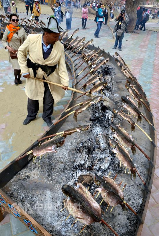 具有防風固沙功能的新疆紅柳樹,因紅柳烤肉走紅出現生態危機。圖為新疆羅布人後裔的傳統烤魚,剖開魚腹後用細紅柳枝攤平,再用胡楊木烘烤。(中新社提供)中央社 107年6月23日