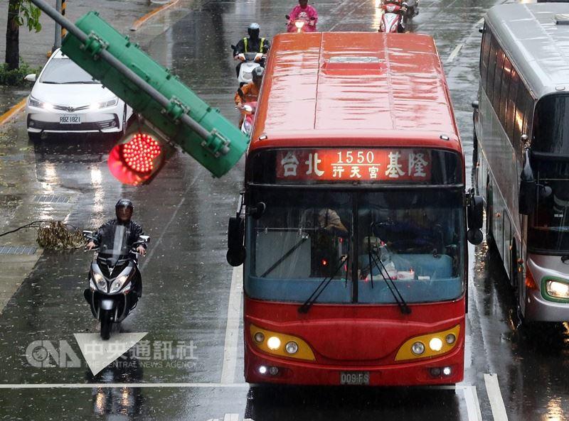 颱風瑪莉亞來襲,新北市政府10日晚間宣布11日停止上班上課,但台北市與基隆市11日則正常上班上課。往來台北市與基隆的公車一早正常發車,不過路口紅綠燈卻因強風歪斜。 中央社記者郭日曉攝 107年7月11日