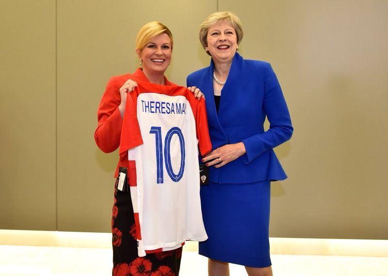 克羅埃西亞總統季塔洛維奇(左)致贈紅白色系的國家代表隊球衣給英國首相梅伊(右)。(圖取自季塔洛維奇推特twitter.com/KolindaGK)