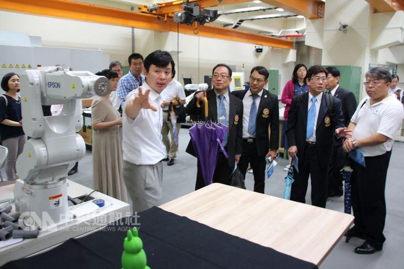 泰國台商代表團12日下午參訪國立中正大學工具機特色實驗室,中正大學前瞻製造系統頂尖研究中心組長林派臣(前左)介紹研究成果。中央社記者江俊亮攝 107年7月12日