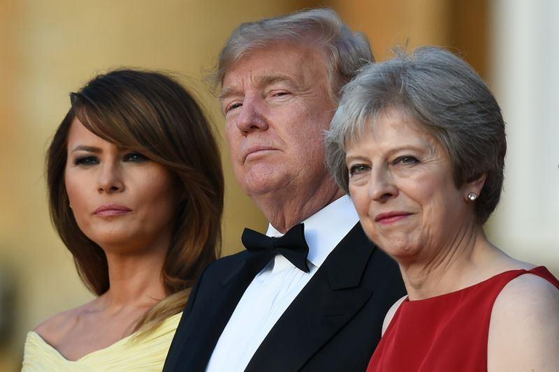 英國首相梅伊(右)12日晚間宴請美國總統川普(中)和第一夫人梅蘭妮亞(左),川普夫婦在蘇格蘭、愛爾蘭和威爾斯衛兵樂隊奏樂歡迎下,抵達國宴現場。(法新社提供)