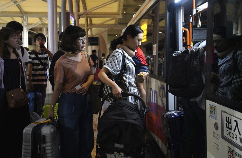 圖為5日關西機場外搭乘巴士以接駁至高速船碼頭的旅客。(檔案照片/共同社提供)