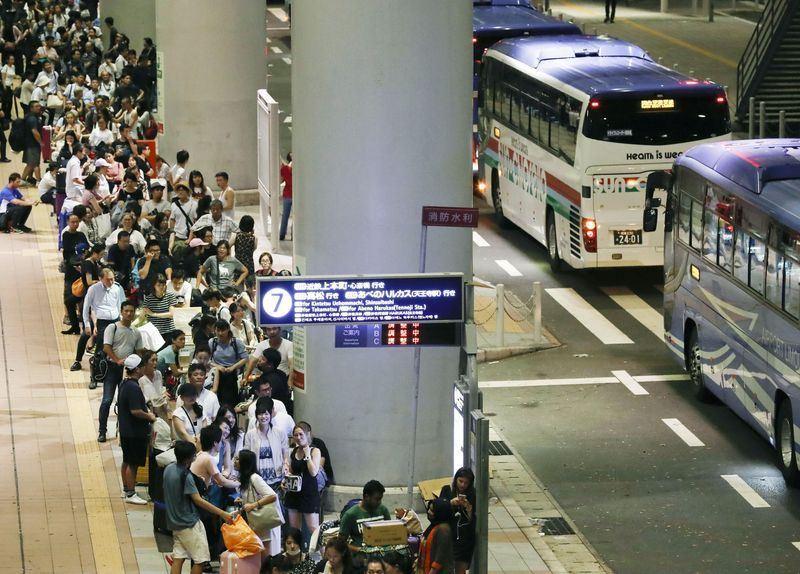 大阪關西機場4日受到颱風燕子的影響,一條跑道淹水,加上郵船撞毀這座人工島的對外聯絡橋梁,造成機場內旅客受困。圖為旅客5日在關西機場排隊等待專車。(檔案照片/共同社提供)